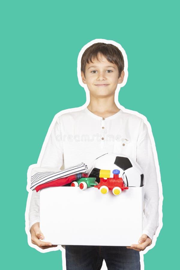 Concept de don Enfant tenant une boîte de don avec vêtements, livres, fournitures scolaires et jouets Style de collage de magazin photo libre de droits