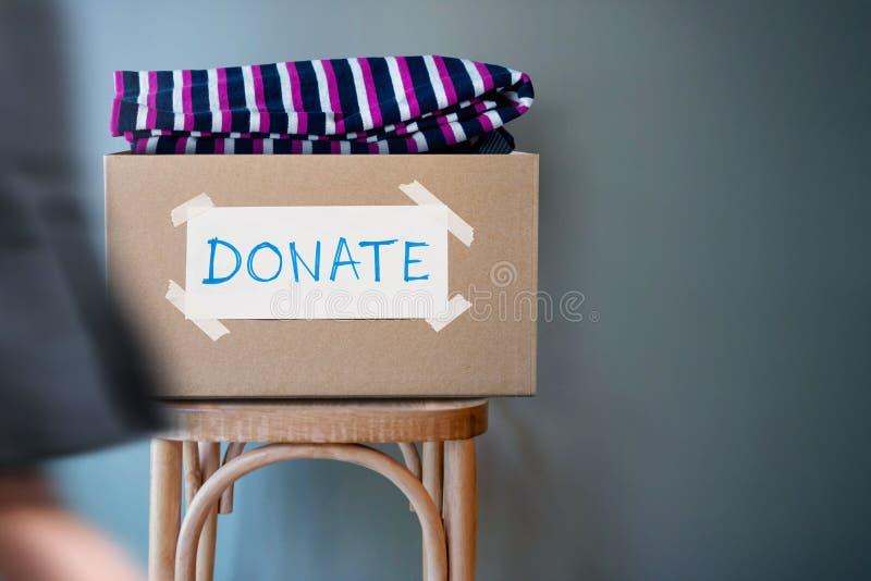 Concept de donation Donnez la boîte avec de vieux vêtements utilisés sur l'agai de chaise photos libres de droits