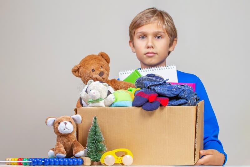 Concept de donation de Noël Se tenir d'enfant donnent la boîte avec des vêtements, des livres et des jouets pour la charité photos stock