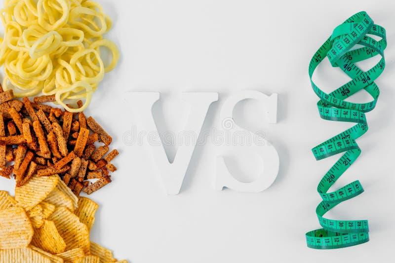 Concept de faire le choix de la nourriture Nourriture malsaine : frites, anneaux de cpackersonion contre la bande de mesure, conf images stock