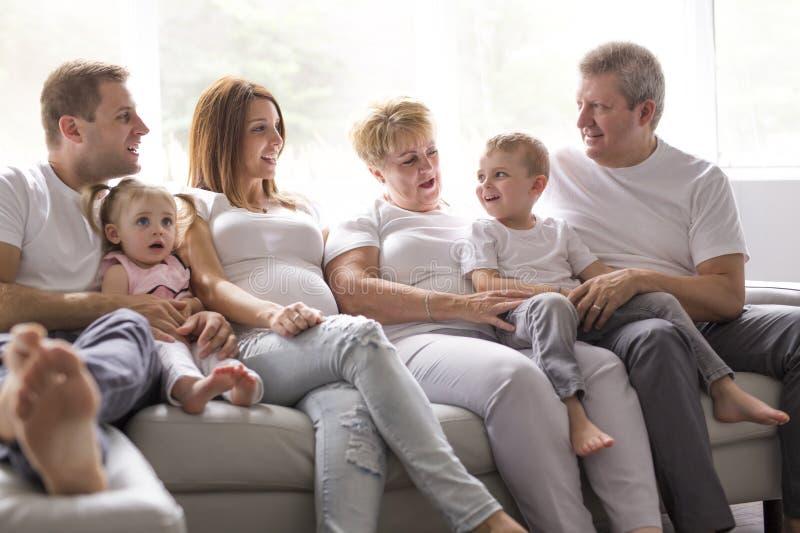Concept de famille, de bonheur, de génération et de personnes sur le sofa images libres de droits