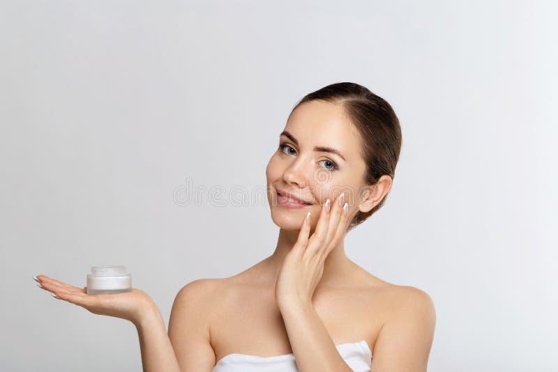 Concept de femme de beauté Soin de peau Jeune modèle avec la peau molle tenant la crème cosmétique Maquillage nu photos libres de droits