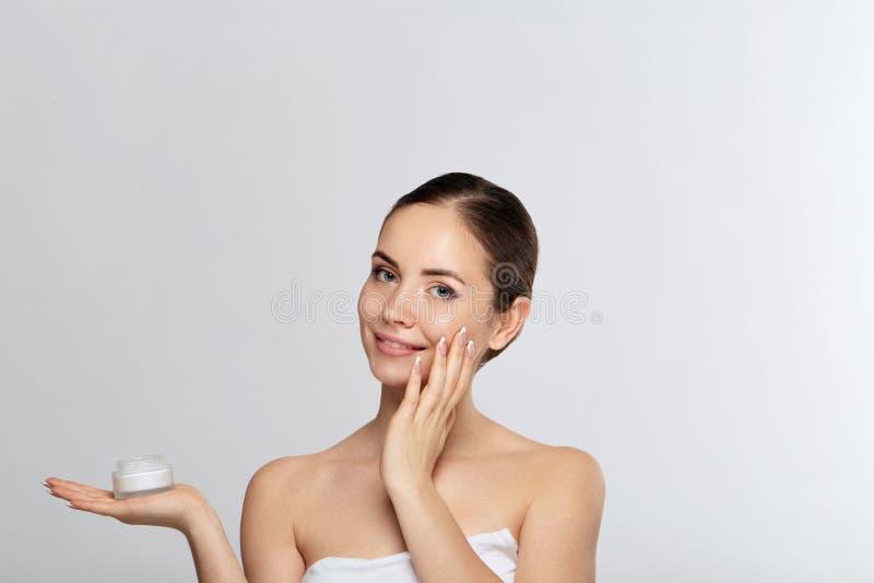 Concept de femme de beauté Soin de peau Jeune modèle avec la peau molle tenant la crème cosmétique Portrait de crème de applicati image stock