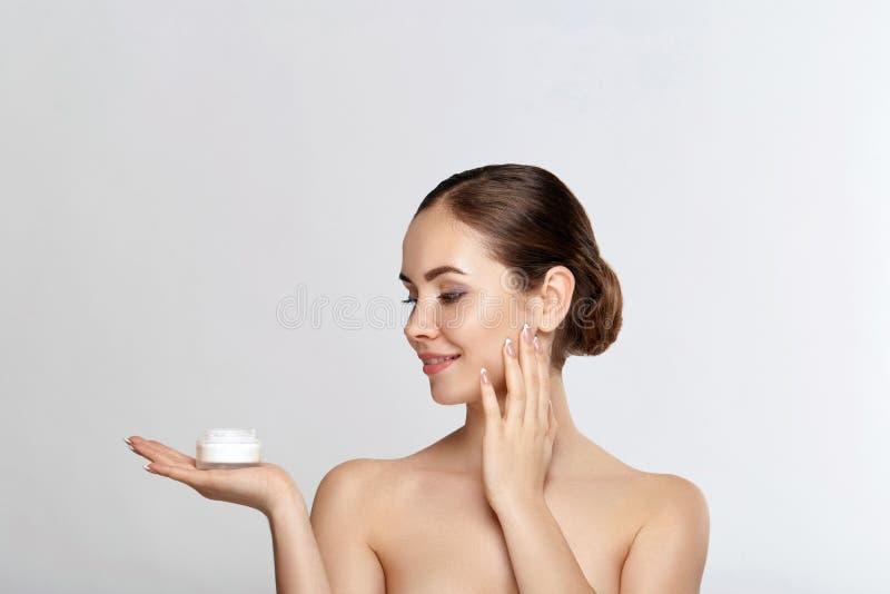 Concept de femme de beauté Soin de peau Jeune modèle avec la peau molle tenant la crème cosmétique Portrait de crème de applicati photos libres de droits