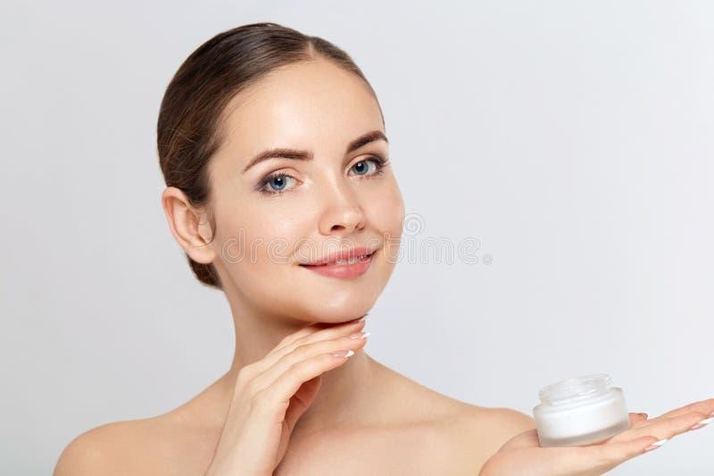 Concept de femme de beauté Soin de peau Jeune modèle avec la peau molle tenant la crème cosmétique Portrait de crème de applicati photo libre de droits
