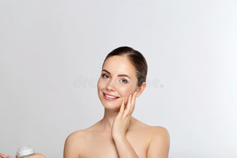 Concept de femme de beauté Soin de peau Portrait de modèle femelle tenant et appliquant la crème cosmétique de hydrater et touche image stock