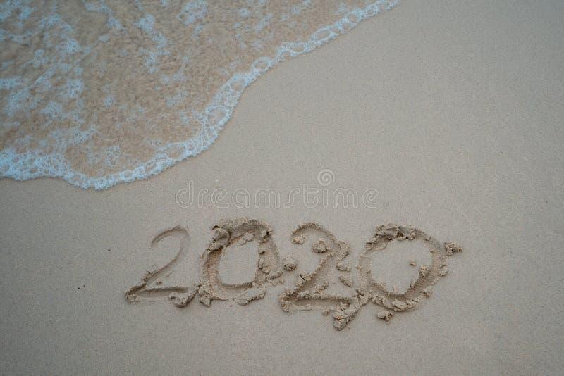 Concept 2020 de fin d'année, lettrage de 2020 nombres sur la plage de mer, vague et lumière d'or de coucher du soleil image libre de droits
