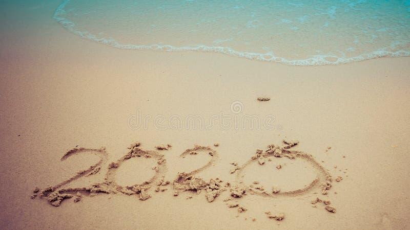 Concept 2020 de fin d'année, lettrage de 2020 nombres sur la plage de mer, vague et lumière d'or de coucher du soleil photo stock