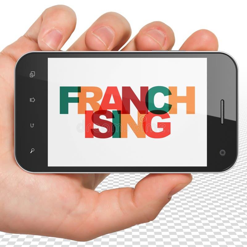 Concept de finances : Main tenant Smartphone avec le franchisage sur l'affichage photos libres de droits