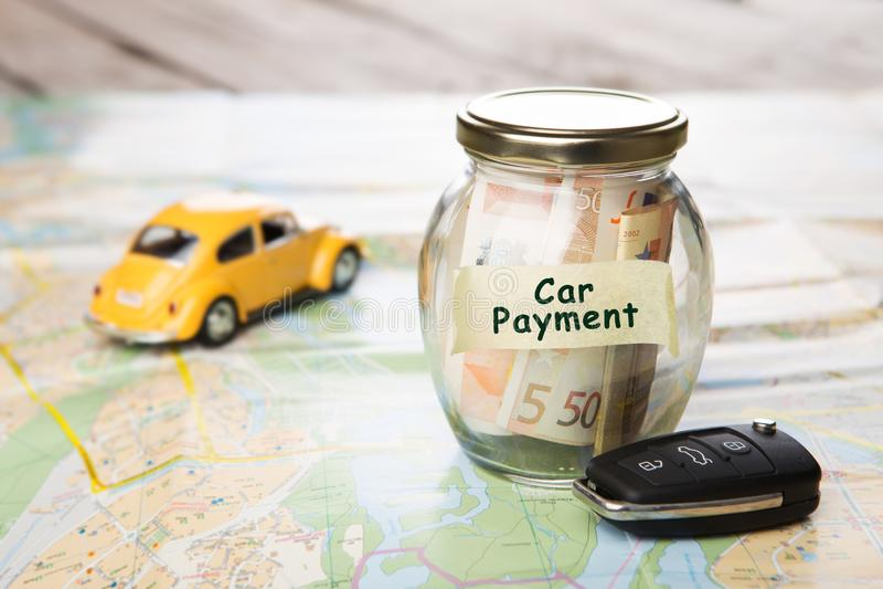 Concept de finances de voiture - verre d'argent avec le paiement de voiture de mot photographie stock