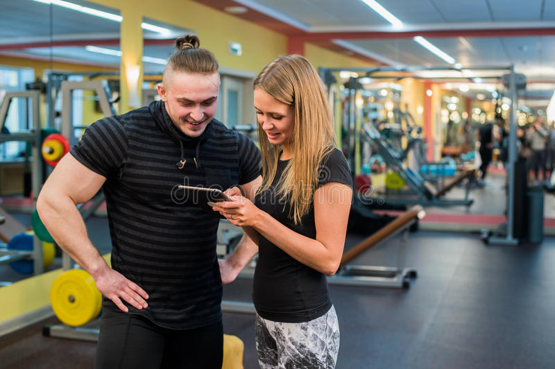 Concept de forme physique, de sport, d'exercice, de technologie et de régime - jeune femme de sourire et entraîneur personnel ave photographie stock libre de droits