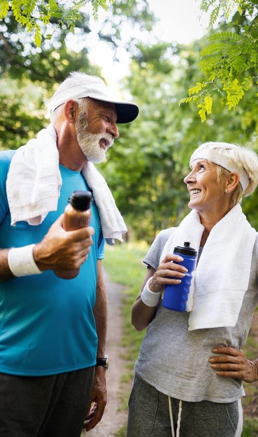 Concept de forme physique, de sport et de mode de vie - couple mûr heureux dans des vêtements de sports dehors photographie stock