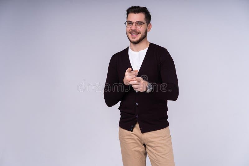 Concept de geste et de personnes - jeune homme de sourire heureux indiquant le doigt vous au-dessus du fond gris photo libre de droits