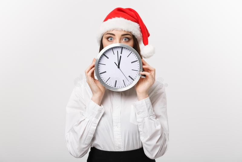 Concept de gestion du temps - jeune femme d'affaires avec le chapeau de Santa se cachant derrière une horloge d'isolement au-dess photo libre de droits