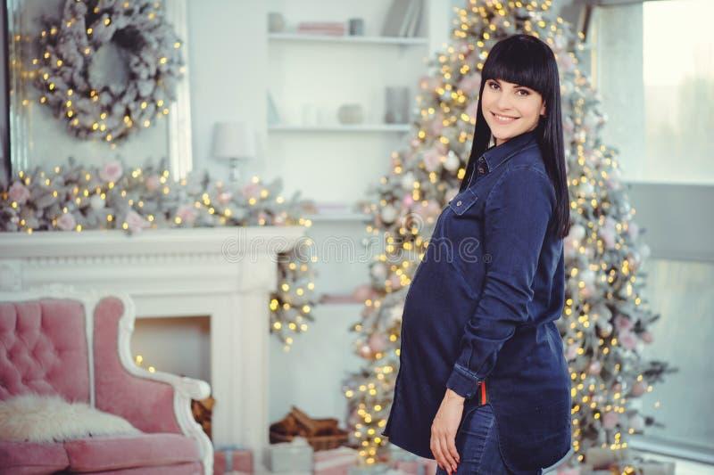 Concept de grossesse, d'amour, de personnes et d'attentes - la femme enceinte heureuse, se tient dans une chambre dans la perspec image libre de droits