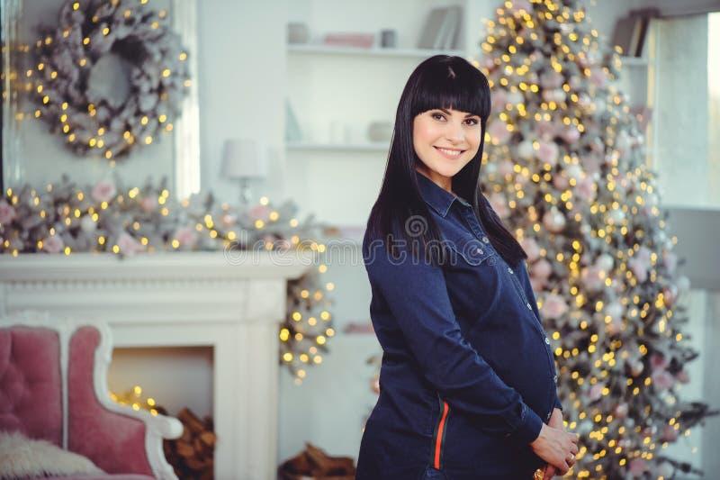 Concept de grossesse, d'amour, de personnes et d'attentes - la femme enceinte heureuse, se tient dans une chambre dans la perspec image stock