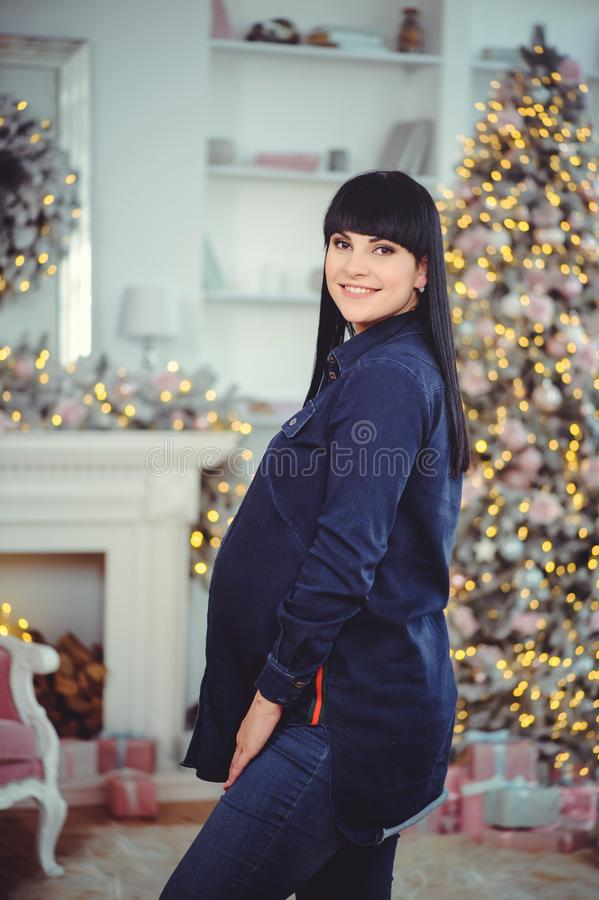 Concept de grossesse, d'amour, de personnes et d'attentes - la femme enceinte heureuse, se tient dans une chambre dans la perspec photographie stock