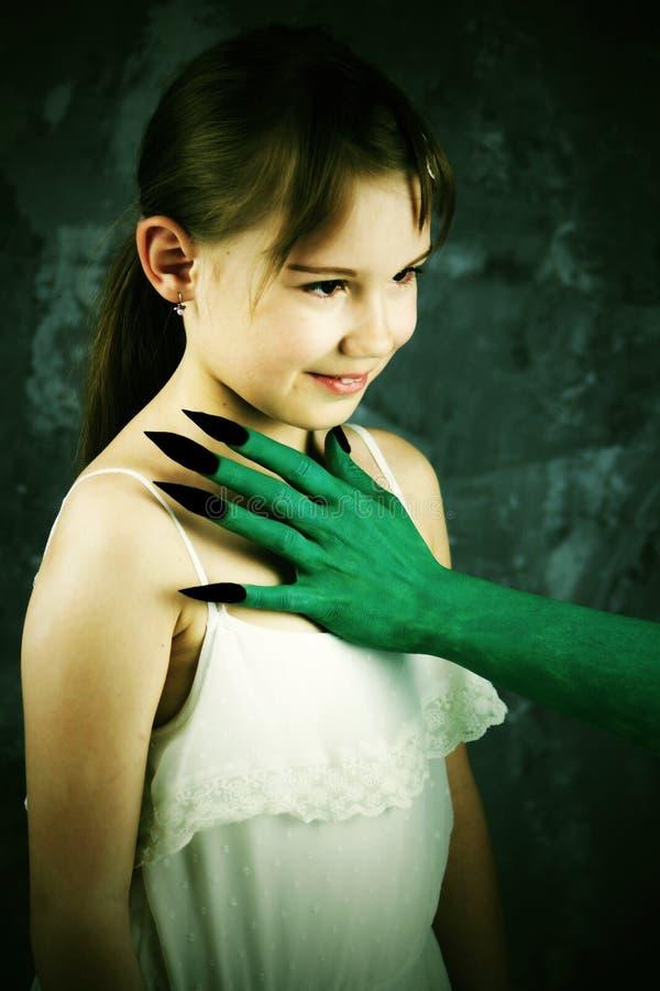 Concept de HALLOWEEN - le ` vert s de sorcière arme avec les clous noirs devant le visage du ` s de fille Le conte de fées de bla photo libre de droits