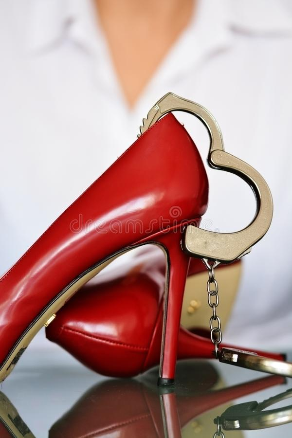 Concept de harcèlement sexuel avec les talons hauts et les menottes rouges images libres de droits