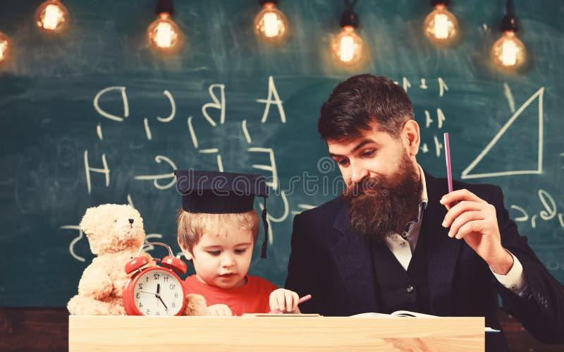 Concept de Hometask Professeur dans le tenue de soir?e et l'?l?ve dans la taloche dans la salle de classe, tableau sur le fond en photographie stock libre de droits