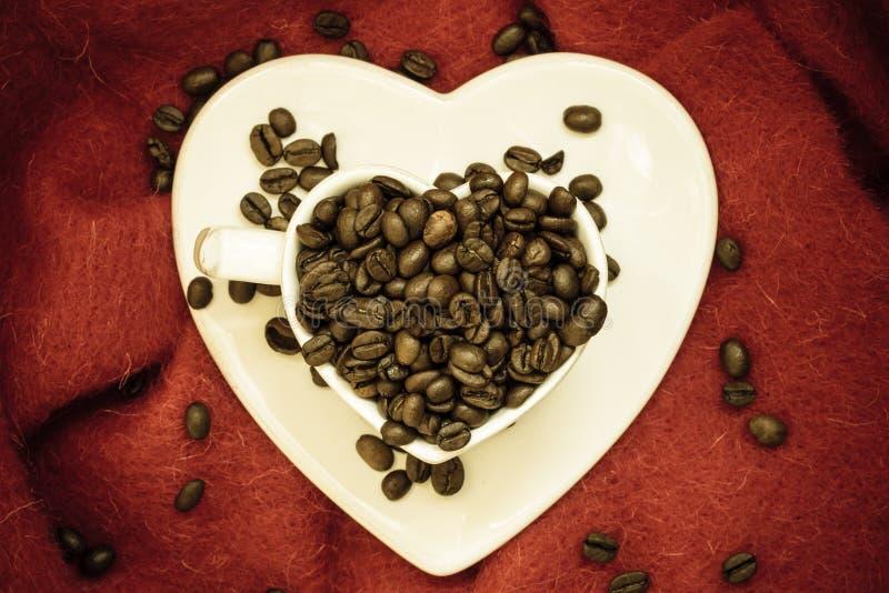 Concept de Java de klatsch de café Tasse en forme de coeur remplie de grains de café rôtis image stock