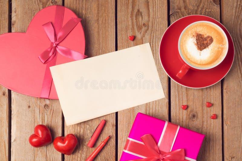 Concept de jour de valentines avec la carte de voeux, le boîte-cadeau et la tasse de café au-dessus du fond en bois Vue supérieur image libre de droits