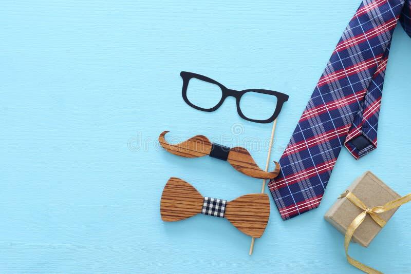 Concept de jour du ` s de p?re Verres de hippie, lien de bo?te de goft et moustache dr?le au-dessus de fond en bois bleu Vue sup? photo stock