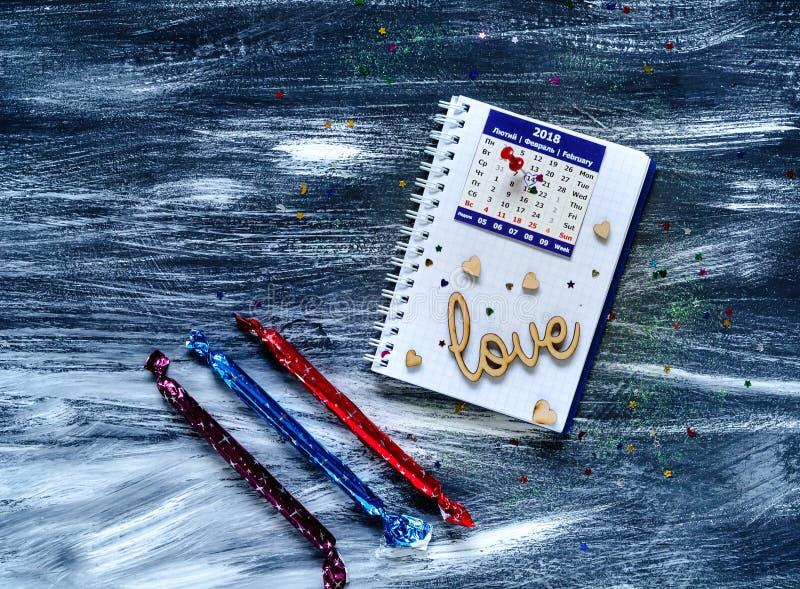 Concept de jour du ` s de Valentine, inscription en bois sur l'amour et coeurs sur un carnet avec un calendrier, lumière naturell images libres de droits