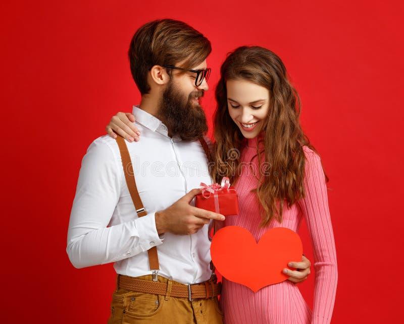 Concept de jour du ` s de Valentine jeunes ajouter heureux au coeur, fleurs, cadeau sur le rouge photos stock