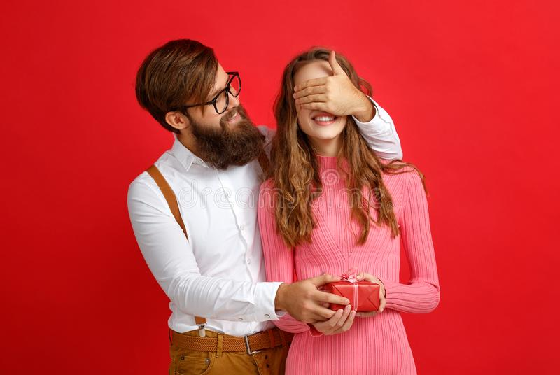 Concept de jour du ` s de Valentine jeunes ajouter heureux au coeur, fleurs, cadeau sur le rouge images stock