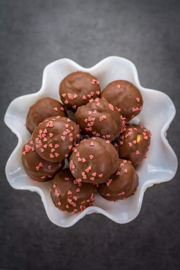 Concept de jour du ` s de Valentine, profiteroles de chocolat avec les coeurs roses photographie stock