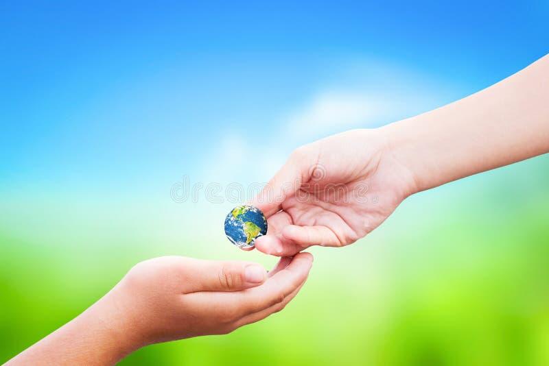 Concept de jour de nourriture du monde : la main tenant le globe de la terre donnent d'autres au-dessus du fond de nature photographie stock