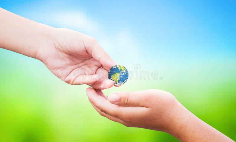Concept de jour de nourriture du monde : la main tenant le globe de la terre donnent d'autres au-dessus du fond de nature photos libres de droits