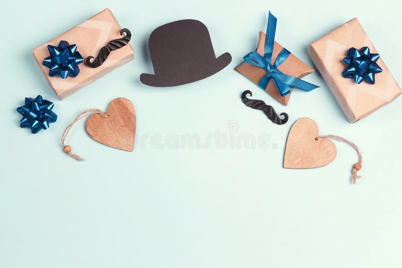 Concept de jour de p?res avec le chapeau de bo?te-cadeau, de moustache et de papier sur le fond bleu images libres de droits