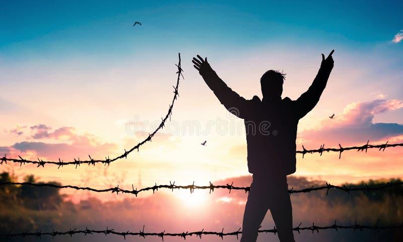 Concept de jour de réfugié du monde : Position d'homme sur le barbelé au fond de coucher du soleil image stock