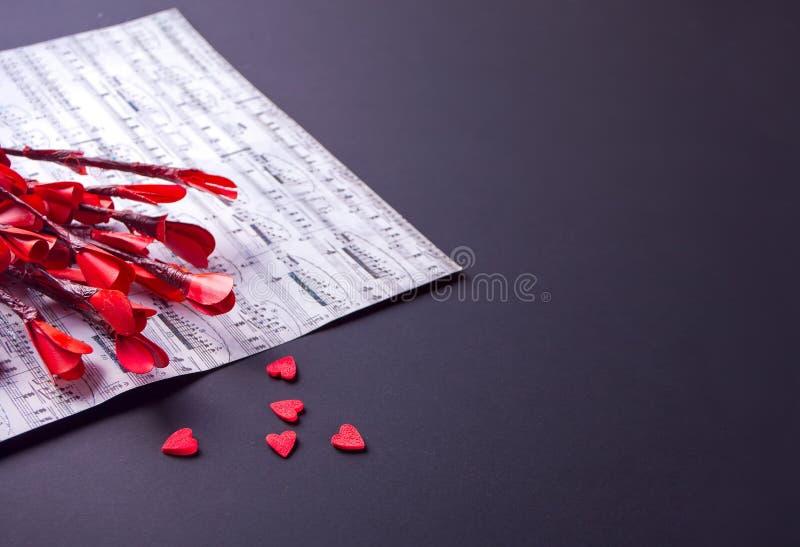 Concept de jour de valentines avec les fleurs, les amoureux de sucrerie et la feuille de musique rouges de papier photographie stock libre de droits
