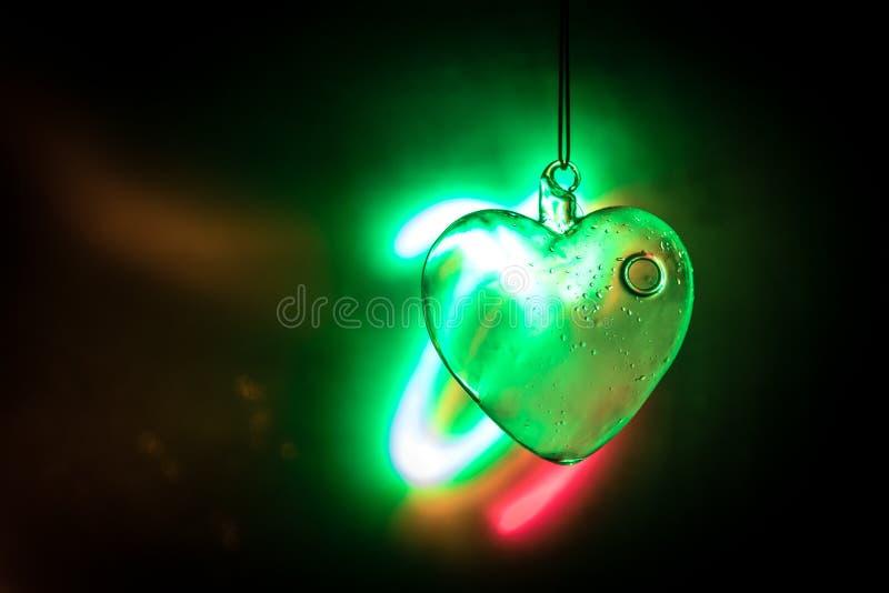 Concept de jour de Valentines Coeur transparent en verre sur l'obscurité Le coeur en cristal au coeur foncé et en verre rougeoie, images stock