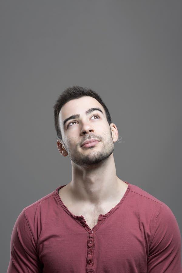 Concept de knappe jonge mens die omhoog hebbend een idee met lege exemplaarruimte kijken stock fotografie