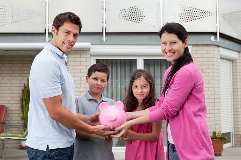 Concept de l'épargne - famille heureuse avec la tirelire photographie stock