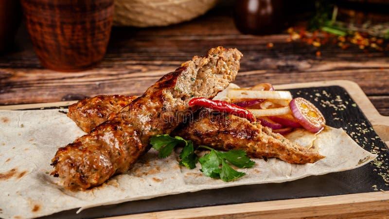 Concept de la cuisine géorgienne Chiche-kebab juteux de lula fait à partir de la viande et des épices Plats de portion dans le re images libres de droits