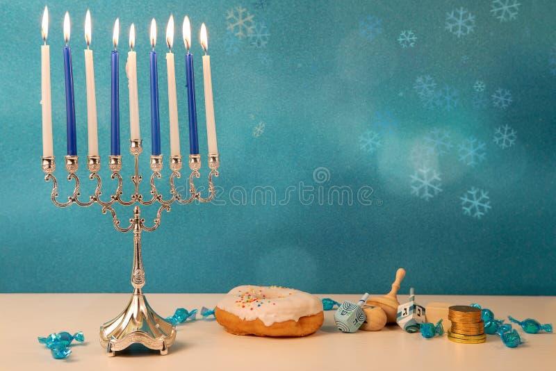 Concept de la fête religieuse juive hanoukkah avec la menorah traditionnelle du lustre, filant de grands jouets rêidel, un beigne image libre de droits