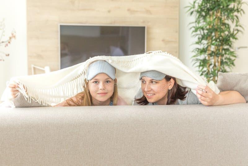 Concept de la famille de happ de mère et de fille masque de port de sommeil et avoir l'amusement sur le sofa dans le salon images libres de droits