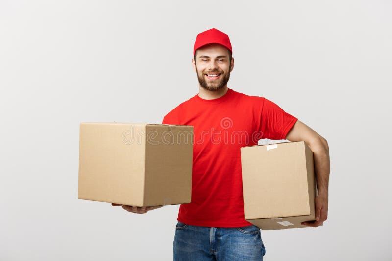 Concept de la livraison : Livreur caucasien beau de sourire tenant une boîte de papier D'isolement au-dessus du fond gris photos libres de droits