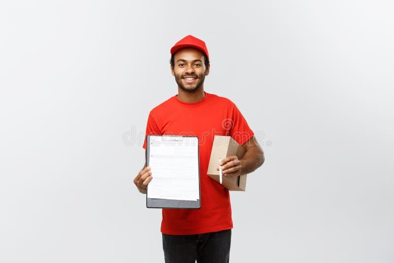 Concept de la livraison - portrait du livreur ou du messager beau d'Afro-américain montrant une forme de document de confirmation images libres de droits