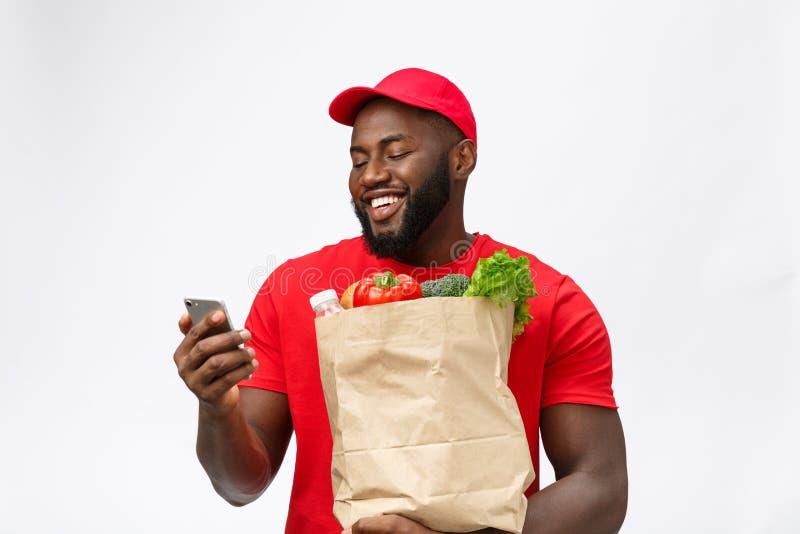 Concept de la livraison - portrait de livreur ou de messager beau d'Afro-américain avec le paquet et parler d'épicerie dessus images libres de droits