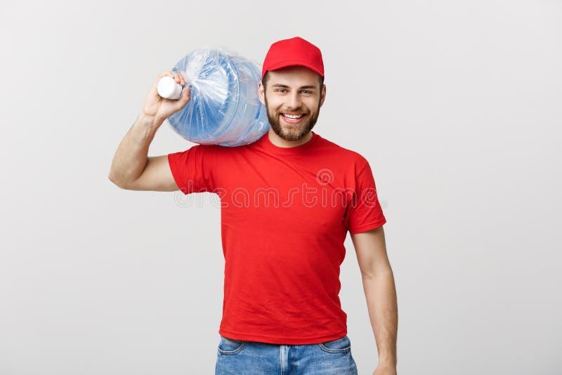 Concept de la livraison : Portrait de messager de sourire de la livraison d'eau en bouteille dans le réservoir de transport rouge photo libre de droits