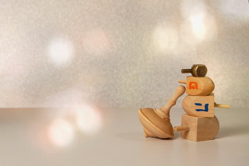 Concept de la religion juive de fête hanukkah avec du bois et du laiton filant des drênes de jouets, sur une table en bois et des images stock