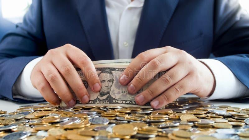 Concept de la richesse et de la richesse Homme d'affaires s'asseyant derrière le bureau couvert de pièces de monnaie et tenant la images stock