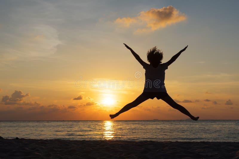 Concept de liberté avec le jeune adolescent de silhouette heureux et le saut photographie stock libre de droits