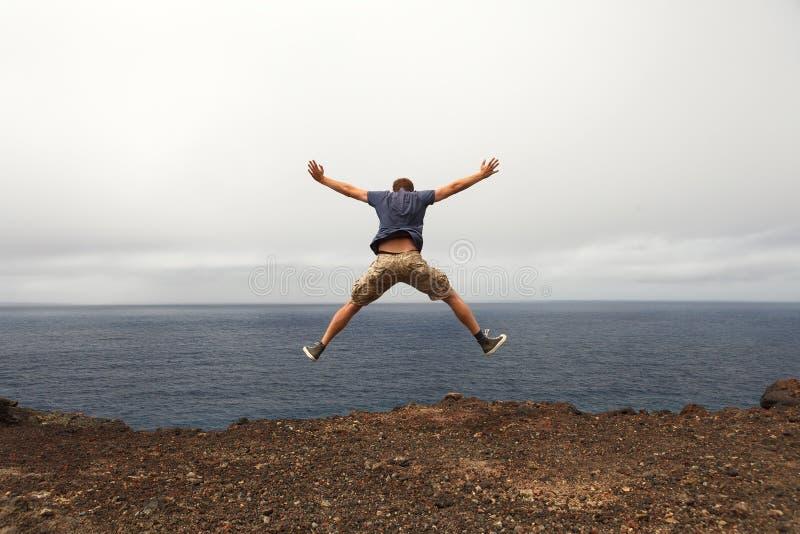 Concept de liberté ou d'aventure - saut de jeune homme images stock